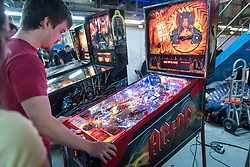 © Licensed to London News Pictures. 12/08/2018. LONDON, UK. A man plays a pinball machine at Play Expo London, a video games show featuring consoles, handhelds, computers, vintage arcades and pinball machines, organised by Replay Events taking place at the Printworks in Canada Water, East London.  Photo credit: Stephen Chung/LNP
