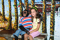 Girl age 7-8-9, poses with a monkey at Samphran Elephant Ground & Zoo Nakhon Pathom province Thailand
