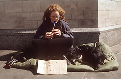 Homeless woman with pet dog sitting in street playing recorder and begging,