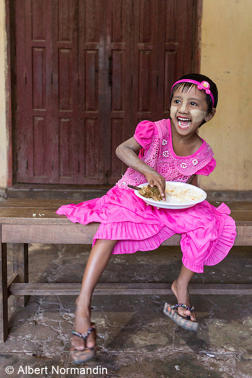 Young happy girl in pink, eating at festival in market,  Hpa-an