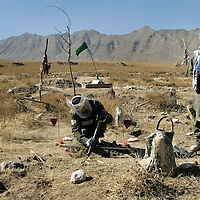 Members of a Halo Trust team searches for mines in a village cemetery. Afghanistan remains one of the most heavily mined countries in the world. A mine clearance team from the Halo Trust have been working for more than a year in the small village of Kohe Safi and have removed 800 mines and 118 unexploded bombs. Kohe Safi, Afghanistan on the 1st of November 2007..Throughout the country the Halo Trust alone is working to clear 90 million square meters of mine fields containing some 640,000 mines, they estimate it will take them 18 years to complete this task..A break through in mine detection not seen since  World War II is due to speed things up in the coming year when Halo become the first civilian organisation to use H-STAMIDS (The Handheld Stand-Off Mine Detection System) a new combination tool with a metal detector and ground penetrating radar system. The H-STAMIDS remain classified and during recent trails in Afghanistan the device had to be returned to the US military at the end of each day. The new equipment should make mine clearance 2-3 times faster.