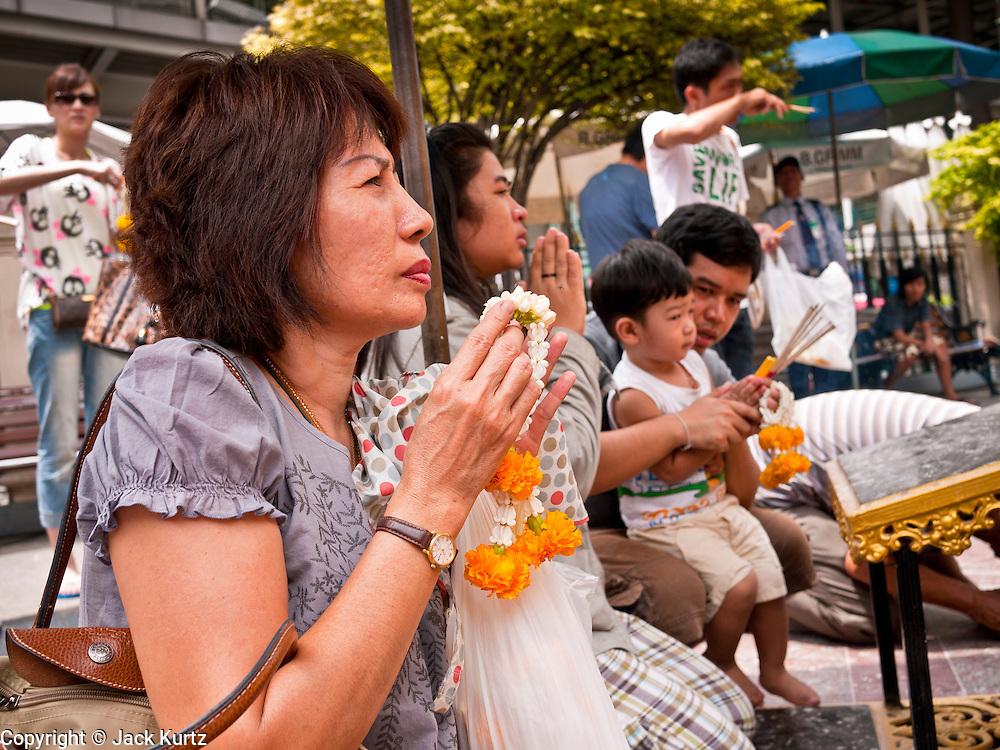 11 JULY 2011 - BANGKOK, THAILAND:   People pray at the Erawan Shrine in Bangkok. The Erawan Shrine (in Thai San Phra Phrom) is a Hindu shrine in Bangkok, Thailand that houses a statue of Phra Phrom, the Thai representation of the Hindu creation god Brahma. A popular tourist attraction, it often features performances by resident Thai dance troupes, who are hired by worshippers in return for seeing their prayers at the shrine answered. On 21 March 2006, a man vandalised the shrine and was subsequently killed by bystanders. The shrine is located by the Grand Hyatt Erawan Hotel, at the Ratchaprasong intersection of Ratchadamri Road in Pathum Wan district, Bangkok, Thailand. It is near the Bangkok Skytrain's Chitlom Station, which has an elevated walkway overlooking the shrine. The area has many shopping malls nearby, including Gaysorn, CentralWorld and Amarin Plaza. The Erawan Shrine was built in 1956 as part of the government-owned Erawan Hotel to eliminate the bad karma believed caused by laying the foundations on the wrong date..The hotel's construction was delayed by a series of mishaps, including cost overruns, injuries to laborers, and the loss of a shipload of Italian marble intended for the building. Furthermore, the Ratchaprasong Intersection had once been used to put criminals on public display. An astrologer advised building the shrine to counter the negative influences. The Brahma statue was designed and built by the Department of Fine Arts and enshrined on 9 November 1956. The hotel's construction thereafter proceeded without further incident. In 1987, the hotel was demolished and the site used for the Grand Hyatt Erawan Hotel.     PHOTO BY JACK KURTZ