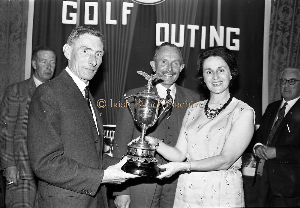 14/05/1965<br /> 05/14/1965<br /> 14 May 1965<br /> Esso Golf Outing at Woodbrook Golf Club, Bray, Co. Wicklow. Mrs J.H. Donovan, wife of the Managing Director of Esso, presenting the Esso Cup and Captains prize to Mr N.P. O'Byrne, Salesman, Cork. In centre is Mr R.A. Drew, Dublin Manager, Esso and Chairman of the Golf Committee.