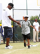 ATLANTA, GA - MAY 14:  Former Major League Baseball player Cliff Floyd  (left) congratulates a young player after he hit a wiffle ball home run during the Wanna Play clinic event during the Civil Rights Youth Summit at Centennial Olympic Park on May 14, 2011 in Atlanta, Georgia.  (Photo by Mike Zarrilli/Getty Images)