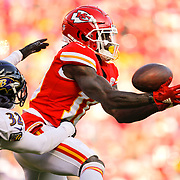 KANSAS CITY, MO - DECEMBER 09: Wide receiver Tyreek Hill #10 of the Kansas City Chiefs reaches for a pass with defensive pressure from free safety Eric Weddle #32 of the Baltimore Ravens at Arrowhead Stadium on December 9, 2018 in Kansas City, Missouri. (Photo by David Eulitt/Getty Images)