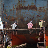 Workers in a boatyard on the Buriganga river in Dhaka, Bangladesh, sitting on a plank while they work