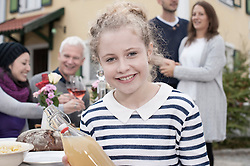 Portrait of a teenage girl holding apple juice and smiling with family in the background, Bavaria, Germany