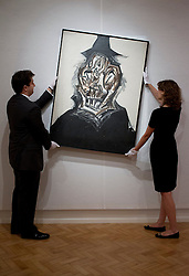 © Licensed to London News Pictures. 08/10/2012. LONDON, UK. Two members of Bonhams staff move Spanish artist Antonio Saura's 'Retrato Imaginario de Felipe II' (1984) (est. GB£120,000-160,000) ahead of a sale at the auction house's New Bond Street premises. The auction, featuring a collection of contemporary art and design is set to take place on Thursday the 11th of October at Bonham's New Bond Street auction house. Photo credit: Matt Cetti-Roberts/LNP