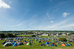 © Licensed to London News Pictures. 24/06/2015. Pilton, UK.   A clear blue over Glastonbury Festival mid morning on  Wednesday Day 1 of the festival.        The Pyramid Stage can be seen, as well as the tents of festivalgoers who arrived early this morning.  The pedestrian gates to the festival opened at 8am this morning, with many festival goers arriving and waiting throughout last night for the opening.  This years headline acts include Kanye West, The Who and Florence and the Machine, the latter having been upgraded in the bill to replace original headline act Foo Fighters.  Photo credit: Richard Isaac/LNP