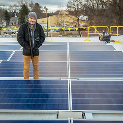 PV Squared employee Michael Suter at a solar panel installation on the roof of a commercial building in Greenfield, Massachusetts.