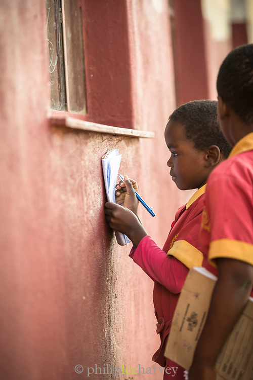Pupil doing school work against wall at local village school in Lubombo Region, Eswatini
