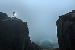 © Licensed to London News Pictures. 10/09/2015. Ilkley, UK. Picture shows an walker on the Cow & Calf rocks at Ilkley moor in the early morning fog. Photo credit: Andrew McCaren/LNP