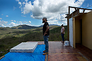 In the wake of  Hurricane Maria, Sammy Luciano surveys the ruined home of his neighbor Diana Ortiz Batiz, right, in the town of Vegas Arriba, in the municipality of Adjuntas, Puerto Rico.