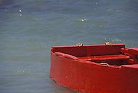 Manos de niño detrás de bote rojo en el mar, Estado Falcón, Venezuela.