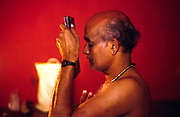 Professor Balasubramanian, a senior teacher of Kathakali prays before starting to apply his make up before a performance at the Kerala Kalamandalam.<br /> The Kalamandalam was founded in 1930 to preserve the cultural traditions of Kathakali, the stylised dance drama of Kerala. Kathakali is the classical dance-drama of Kerala, South India, which dates from the 17th century and is rooted in Hindu mythology. Kathakali is a unique combination of literature, music, painting, acting and dance performed by actors wearing extensive make up and elaborate costume who perform plays which retell in dance form stories from the Hindu epics.