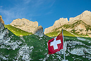 Swiss flag at Meglisalp, Alpstein range, Appenzell Alps, Switzerland, Europe. The flag of Switzerland is red with a white equilateral cross in the center. It is one of only two square sovereign-state flags (the other being the flag of Vatican City). In contrast, the civil and state ensign of Switzerland, used by Swiss vessels and non-governmental bodies, is rectangular with the more common proportions of 3:2. Use of the white cross as a military ensign (attached to the cantonal flags in the form of strips of linen) has been used in the Old Swiss Confederacy since the 1300s, but the modern design was first used in 1800 during Napoleon's Hundred Days, and was introduced as official national flag in 1889. Berggasthaus Meglisalp can only be reached on foot in the heart of the Alpstein mountain chain. This authentic mountain hostelry, owned by the same family for five generations, dates from 1897. Meglisalp is a working family dairy farm.