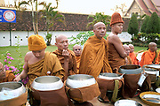 "Buddhist monks collecting alms at the That Luang festival, Vientiane, Lao PDR. Pha That Luang is the national symbol and most important religious monument of Laos. Vientiane's most important Theravada Buddhist festival, ""Boun That Luang"", is held here for three days during the full moon of the twelfth lunar month (November). Monks and laypeople from all over Laos congregate to celebrate the occasion with three days of religious ceremony followed by a week of festivities, day and night. The procession of laypeople begins at Wat Si Muang in the city centre and proceeds to Pha That Luang to make offerings to the monks in order to accumulate merit for rebirth into a better life. The religious part concludes as laypeople, carrying incense and candles as offerings, circumambulate Pha That Luang three times in honor of Buddha."