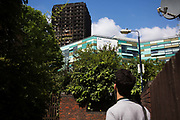 Passers-by stop and watch at the burned out tower June 16th 2017, London, United Kingdom. Grenfell Tower burned out after a catastophic fire killing more than 58 people. The tower caught fire early Wednesday morning and final casualty figueres may end up to be many more with police not expecting to be able to find and recover all bodies and to find all missing people. No fire sprinkler in place and cheap cladding made with plastic is so far blamed for the ferocious fire.