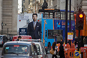 Fashion ad for Italian menswear retailer Boggi on the back of a tourist bus in the City of London. As the tour bus turns a corner, the male model stares backwards as other people walk across theis busy junction in the heart of the capital's financial district, known as Cornhill triangle.