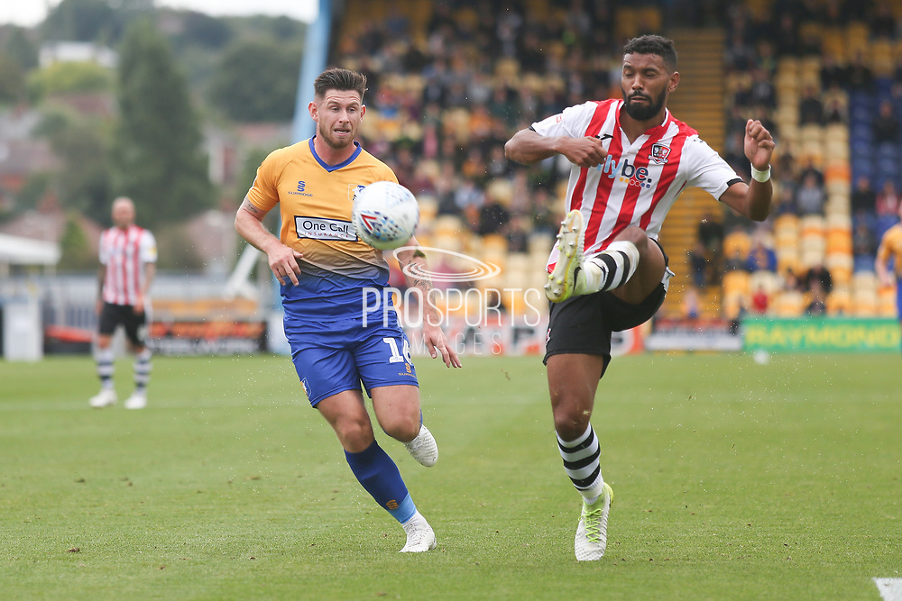 Luke Croll of Exeter City (23) clears from Calum Butcher of Mansfield Town (16) during the EFL Sky Bet League 2 match between Mansfield Town and Exeter City at the One Call Stadium, Mansfield, England on 15 September 2018.
