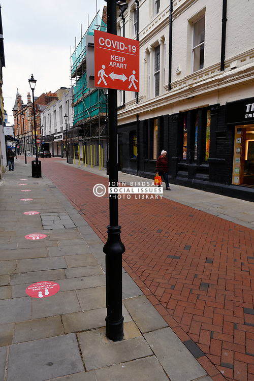 Covid-19 advisory sign and pavement 2 metre spacers in front of bank at left. Easing of Coronavirus lockdown, Reading, UK 12 June 2020