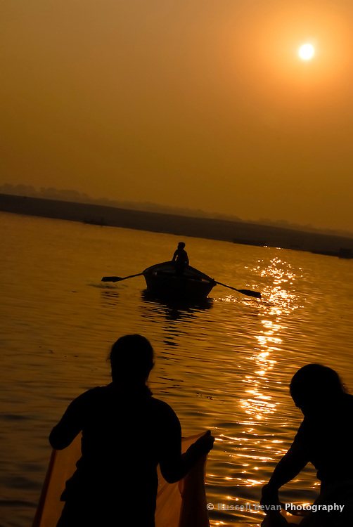 Two women washing while a boatman goes to work in Varanasi, Uttar Pradesh, India