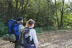 Young couple walking with backpack in a forest, Bavaria, Germany