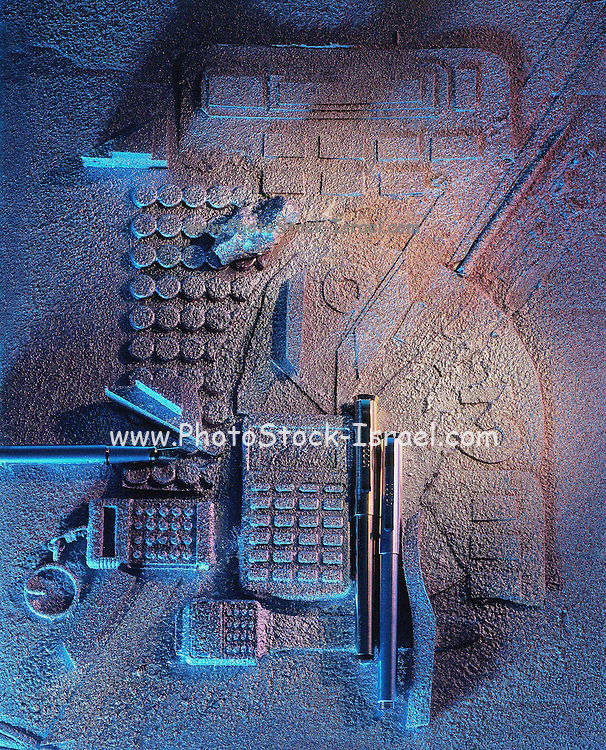 Calculators and electronic gadgets covered in sand to resemble an archaeological find