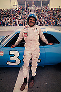 """Wendell Scott during the filming of the movie """"Greased Lightning"""" based on his NASCAR career. Wendell Oliver Scott (August 29, 1921 – December 23, 1990) was an American stock car racing driver. He was one of the first African-American drivers in NASCAR, and the first African-American to win a race in the Grand National Series, NASCAR's highest level.<br /> <br /> Scott began his racing career in local circuits and attained his NASCAR license in around 1953, making him the first African-American ever to compete in NASCAR. He debuted in the Grand National Series on March 4, 1961, in Spartanburg, South Carolina. On December 1, 1963, despite being considered part of the 1964 season, he won a Grand National Series race at Speedway Park in Jacksonville, Florida, becoming the first black driver to win a race at NASCAR's premier level.[3] Scott's career was repeatedly affected by racial prejudice and problems with top-level NASCAR officials. However, his determined struggle as an underdog won him thousands of white fans and many friends and admirers among his fellow racers. He was posthumously inducted into the NASCAR Hall of Fame in 2015."""
