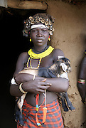 Africa, Ethiopia, Omo Valley, Dassenech tribe woman holding kid goat in front of her hut