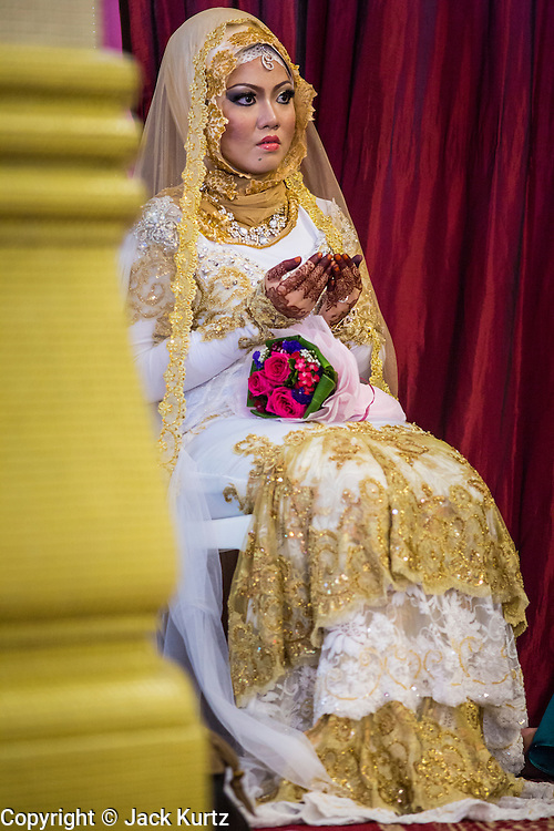 22 DECEMBER 2012 - SINGAPORE, SINGAPORE:  The bride prays during her wedding in the Sultan Mosque in Singapore. The Sultan Mosque is the focal point of the historic Kampong Glam area of Singapore. Also known as Masjid Sultan, it was named for Sultan Hussein Shah. The mosque was originally built in the 1820s. The original structure was demolished in 1924 to make way for the current building, which was completed in 1928. The mosque holds great significance for the Muslim community, and is considered the national mosque of Singapore. It was designated a national monument in 1975.           PHOTO BY JACK KURTZ