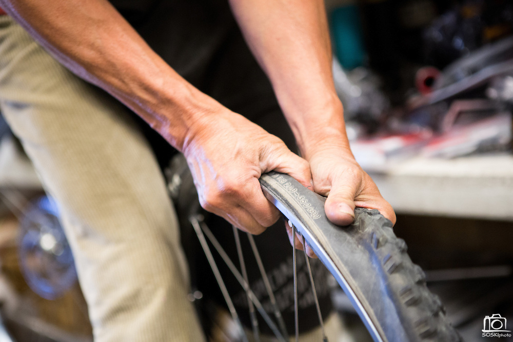 Manager and mechanic Jason Tran removes old tires from a set of damaged wheels on a customer's mountain bike at Sun Bike Shop in Milpitas, Calif., on Sept. 18, 2012.  Tran has been running Sun Bike Shop for over 12 years.  Photo by Stan Olszewski/SOSKIphoto.