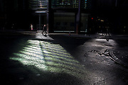 In strong sunlight, pedestrians walk through an area of reflected light in the financial City of London's Threadneedle Street, still wet after recent showers.