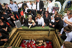 © Licensed to London News Pictures. 21/04/2018. London, UK. Mourners gather at the graveside over the coffin at the burial of traveller 'Queenie, Elizabeth Doherty at Kensal Green Cemetery in west London, following a funeral service in Cobham, Surrey. Elizabeth Doherty, whose son Paddy Doherty is known for appearing on My Big Fat Gypsy Wedding and winning Celebrity Big Brother 8, died of a heart attack earlier this month. Paddy Doherty claimed his mother has died of a 'broken heart' following the death of her husband almost a year ago. Photo credit: Ben Cawthra/LNP