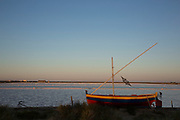 Small sail boat at the famous salt flats at Gruissan, Languedoc-Roussillon, France. This area is very well known for producing sea salt from it's salt fields or marshes on this coastline.
