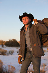 rugged cowboy with a saddle over his shoulder at sunset