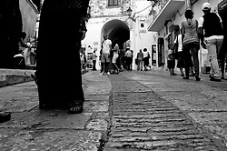 Prospettiva di Via Cattedrale in Ostuni. Alcuni turisti fotografano, altri osservano le vetrine di Souvenir; altri si fermano a chiacchierare
