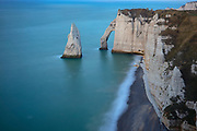 The sea arch Porte d'Aval and the sea stack L'Aiguille (the Needle) stand in the Atlantic Ocean next to the cliffs of Étretat in Normandy, France. Porte d'Aval is most-widely known of the three natural sea arches that have formed in the white chalk cliffs, known as the Falaise d'Étretat, which are as tall as 90 meters (300 feet). L'Aiguille, or the Needle, rises 70 meters (230 feet) above the sea.