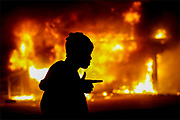 A man walks past a burning building during rioting after a grand jury returned no indictment in the shooting of Michael Brown in Ferguson, Missouri, early November 25, 2014. Gunshots were heard and bottles were thrown as anger rippled through a crowd outside the Ferguson Police Department in suburban St. Louis after authorities on Monday announced that a grand jury voted not to indict a white officer in the August shooting death of an unarmed black teen. REUTERS/Jim Young