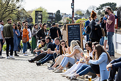 Licensed to London News Pictures. 18/04/2021. London, UK. Pub goers enjoy a drink and soak up the sunshine along the Thames at Richmond, South West London on the first weekend of the easing of Covid-19 restrictions. Shops, pubs, bars and restaurants are now serving customers for the first time in over 4 months as a mini heatwave is set to hit the UK this week with temperatures predicted to reach up to 18c in London and the South East. Photo credit: Alex Lentati/LNP