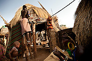 Jie women prepare to leave their village for the  more protected cattle camp in case of violence between the tribes warriors and the Murle in Jonglei state, Southern Sudan.