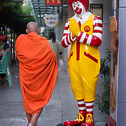 A Theravada Buddhist monk walks by a McDonalds store in Bangkok that honours the dominant religion of Thailand  (Leica 240 MP with 50 mm APO Summicron)