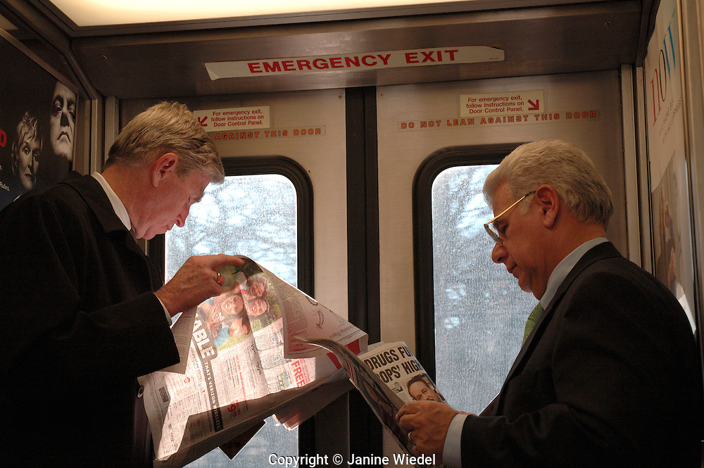 Commuters  reading newspapers travelling into New York by train to work in the city.