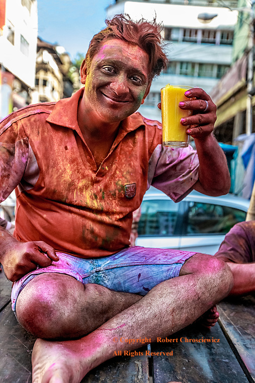 Happy Holi Day: This painted man sits drinking his orange juice, as he pauses his celebration during the Holi Festival that commemorates the victory of good over evil, Kolkata (Calcutta) India.
