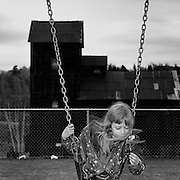 Lola Angus on a grade school swing in the playground adjacent to the Right of Way Mine property, Cobalt, Ontario. From the book Cage Call: Life and Death in the Hard Rock Mining Belt. An in-depth project spanning over 12-years examining communities in one of the richest mining regions in the world located in Northwestern Ontario and Northeastern Quebec in Canada.