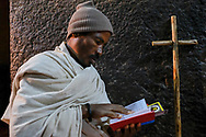 An Orthodox Christian pilgrim is reading the scriptures inside Bet Maryam church in Lalibela. Thousands of pilgrims from all over Ethiopia flock to pray in the famous rock-hewn churches every year.