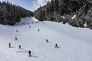 Skiers run down the ski slopes of Bansko ski area