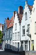 Traditional architecture painted houses with crow-stepped gables - crow steps - in empty street in Bruges, Belgium