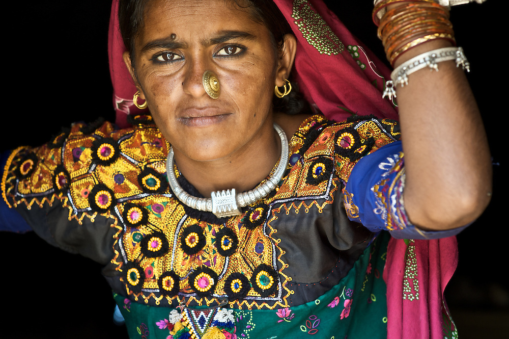 This woman was in traditional finery in a doorway of a small thatch-roofed hut in the remote Thar Desert of Rajasthan, India