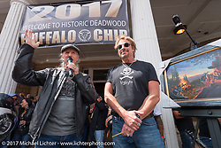 Pat Simmons of the Doobie Brothers with painter David Uhl as a print of David's painting of Pat gets auctioned before the Legends Ride on Main Street in Deadwood during the annual Sturgis Black Hills Motorcycle Rally. Deadwood, SD, USA. Monday August 7, 2017.  Photography ©2017 Michael Lichter.